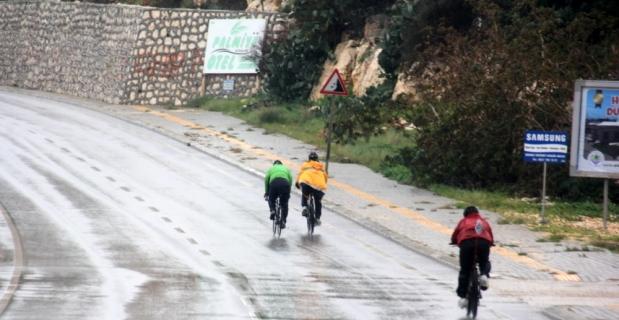 Yağmurda bisiklet sürüp denize girdiler