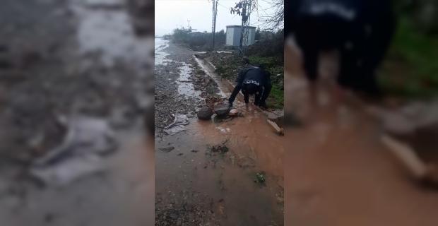 Hatay'da yağış nedeniyle tıkanan su kanalını polis memuru açtı